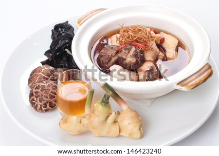 Traditional Chinese herbal soup with chicken and raw ingredients on the side