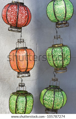 Traditional Chinese lanterns hanging against an old gray wall - stock photo