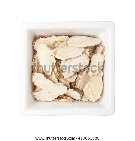 Traditional Chinese Medicine - Sliced ginseng in a square bowl isolated on white background - stock photo