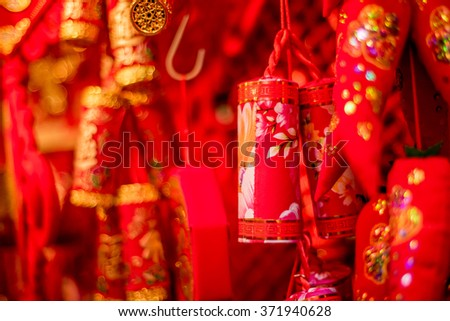 Traditional Chinese new year decorations. Chinese red firecrackers and red peppers. Red background. - stock photo