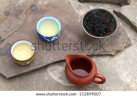 Traditional chinese tea ceremony accessories (cups, puer tea and pitcher) on the stone table, selective focus on cups and pitcher