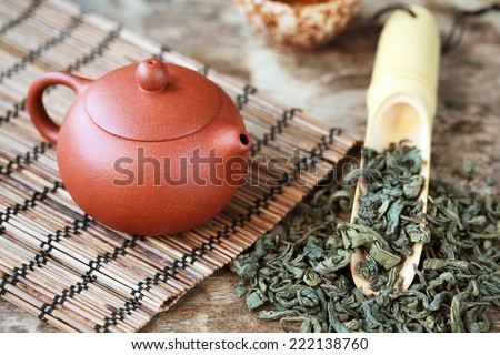 Traditional chinese tea ceremony accessories: tea pot, cup and green tea on the wooden table, selective focus��± toned  - stock photo