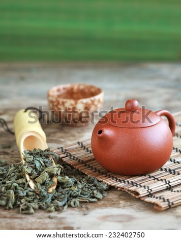 Traditional chinese tea ceremony accessories: tea pot, cup and green tea on the wooden table, selective focus. Toned - stock photo