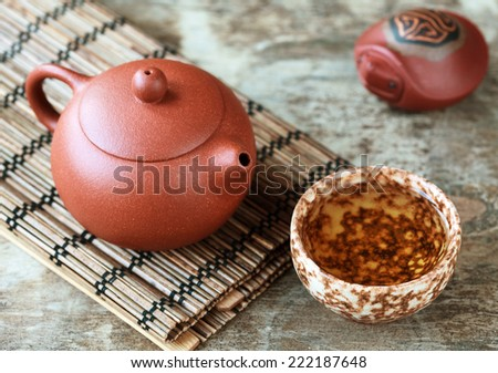 Traditional chinese tea ceremony accessories: tea pot, cup, green tea and clay turtle on the wooden table, selective focus on pot. Toned - stock photo