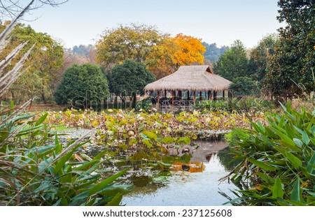 Traditional Chinese Wooden gazebo on the coast. Walking around famous West Lake park in Hangzhou city center, China - stock photo