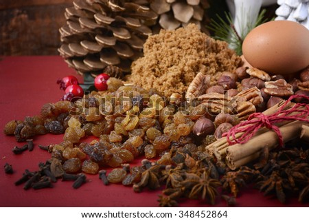 Traditional Christmas festive ingredients including eggs, dried fruit, nuts, brown sugar and spices for plum pudding, fruit cake and mince pies.  - stock photo