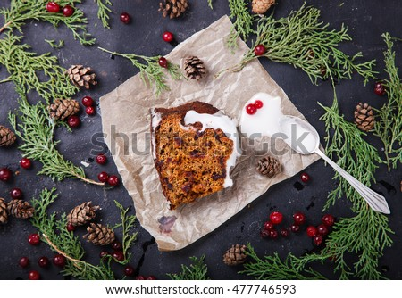Traditional Christmas Fruit Cake pudding with marzipan and cranberry in the glaze decor on a Christmas decoration background.selective focus.