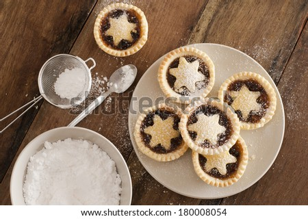 Traditional Christmas fruit mince pies decorated with pastry stars on a kitchen table ready to be sprinkled with powdered icing sugar in a sieve for a delicious seasonal teatime snack, overhead view - stock photo