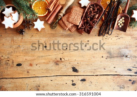 Traditional Christmas spices and cookies arranged as a top border over rustic wood background with cinnamon, star anise, speculoos and star biscuits and dried orange slices, large copyspace - stock photo