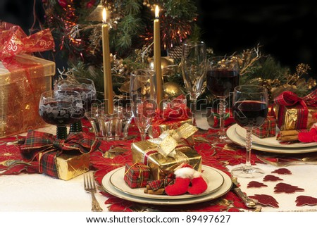 Traditional Christmas table setting with tree, presents, candles, lights, cracker, and red wine, - stock photo