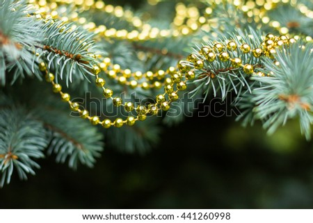 Traditional christmas tree decorated with golden garland, selective focus - stock photo