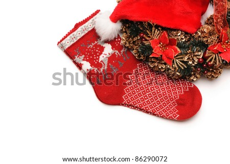 Traditional christmas wreath with santa hat an stocking isolated on white - stock photo