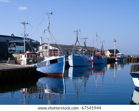 Traditional classical design fishing boats in a port with reflection in the water - stock photo
