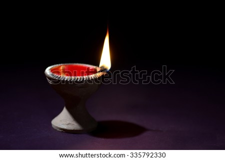 Traditional clay diya lamps lit during Diwali celebration - stock photo