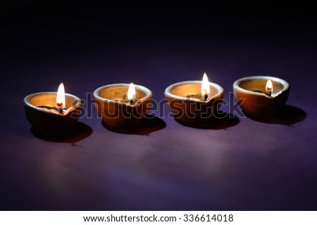 Traditional clay Diya (Lantern) lamps lit during Diwali celebration. Greetings Card Design Indian Hindu Light Festival called Diwali - stock photo