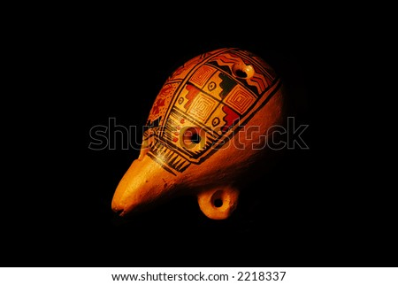 Traditional clay painted ocarina on black background - stock photo