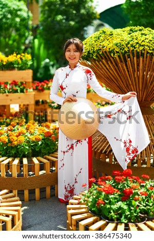 Traditional Clothing Of Vietnam, Asia. Beautiful Happy Asian Girl Dressed In National Traditional Ao Dai Dress ( Costume ), Vietnamese Conical Hat ( Non La, Leaf Hat )