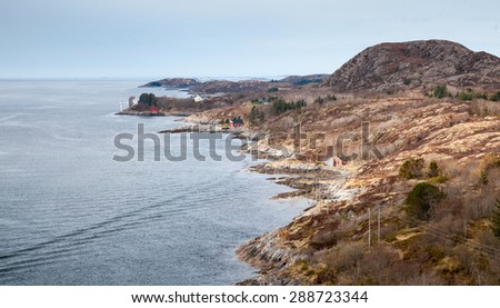 Traditional coastal Norwegian village with colorful wooden houses on coastal cliffs - stock photo