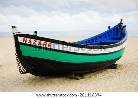 Traditional colorful  boat on the beach of Nazare (Portugal) - stock photo