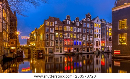 Traditional colorful canal houses at night seen from the Sint Olofsteeg on the Oudezijds Voorburgwal in the UNESCO World Heritage site of Amsterdam - stock photo