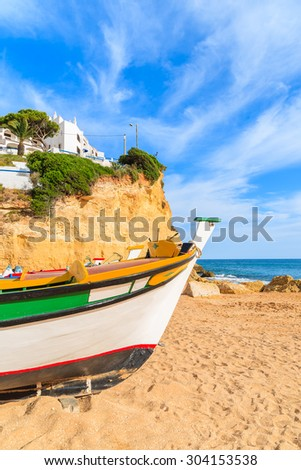 Traditional colourful fishing boat on beach in Carvoeiro village, Algarve region, Portugal