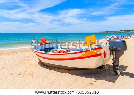 Traditional colourful fishing boat on sandy beach in Armacao de Pera village, Algarve region, Portugal - stock photo