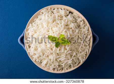 traditional cooked plain white basmati rice, served in a blue bowl with a mint leaf on top, top angle, closeup on blue background - stock photo