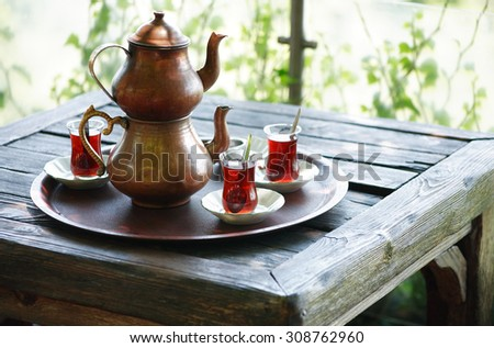 Traditional copper Turkish teapot in summer outdoor cafe - stock photo
