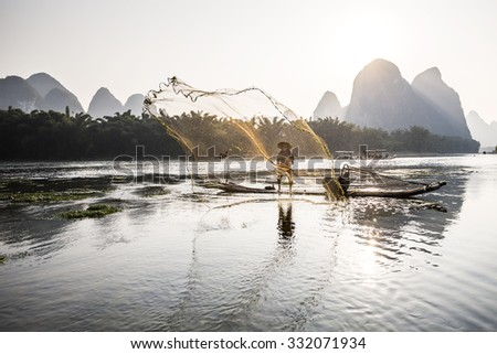 traditional cormorant fisherman throwing a net on Li river near Xingping, Guangxi province, China. - stock photo