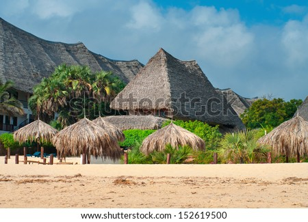 Traditional cottage between palm trees on the beach