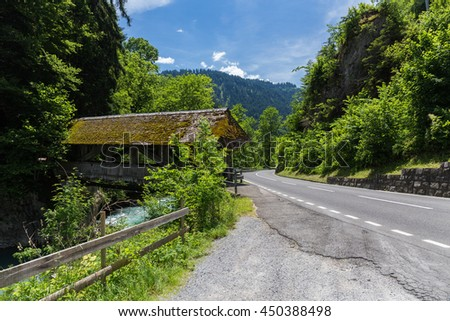 Traditional Covered Wood Bridge in mountain Switzerland - stock photo