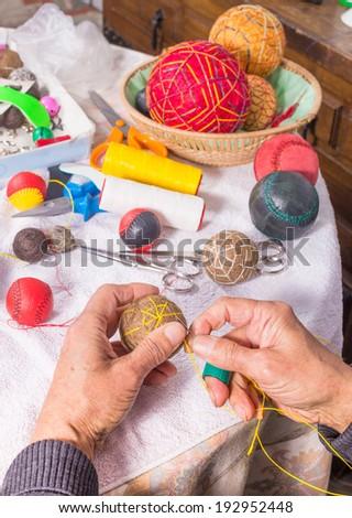 Traditional craft, hands sewing a jai alai ball - stock photo