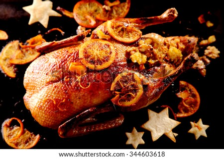 Traditional crispy marinated roasted Christmas turkey with tasty stuffing and orange garnish served with festive pastry stars, view from above - stock photo