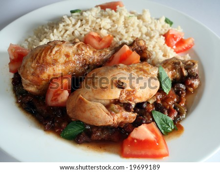 Traditional Cuban chicken drumsticks in black bean and tomato sauce, served with brown rice. - stock photo