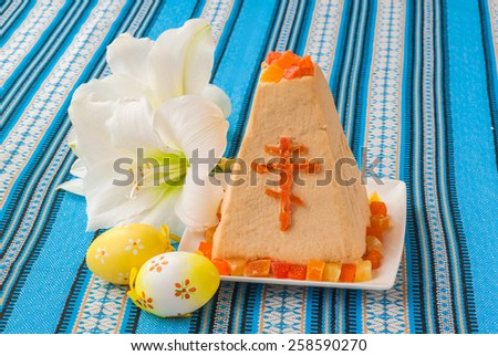 Traditional curd Easter cake on embroidered tablecloth next to the white flower and eggs - stock photo