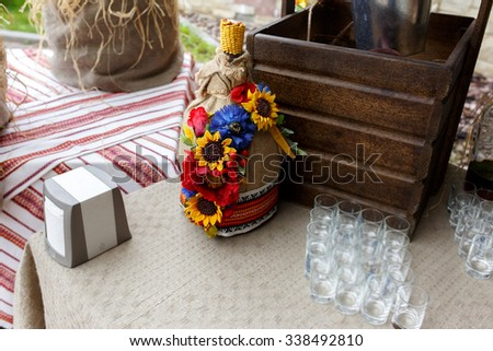 Traditional decorated with sunflowers and red floral ornaments ukrainian bottle on a vintage background - stock photo