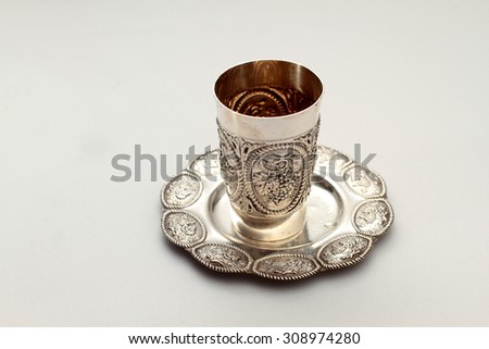 Traditional, decorative Jewish kiddush cup. Silver cup with saucer filled to the brim with purple wine isolated on a white background