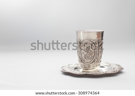 Traditional, decorative Jewish kiddush cup. Silver cup with saucer filled to the brim with purple wine isolated on a white background - stock photo