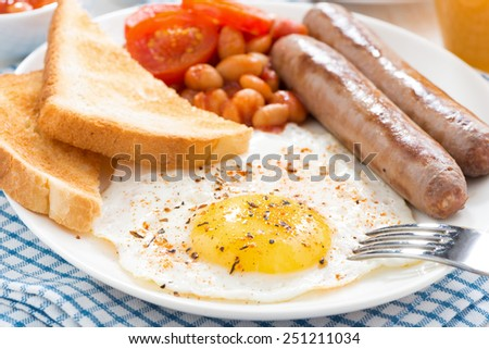 Traditional delicious English breakfast with sausages, close-up, horizontal - stock photo