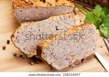 Traditional delicious meat pate with vegetables on wooden board