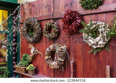 Traditional design of a christmas wreaths attached to the door of old house from different natural materials - stock photo