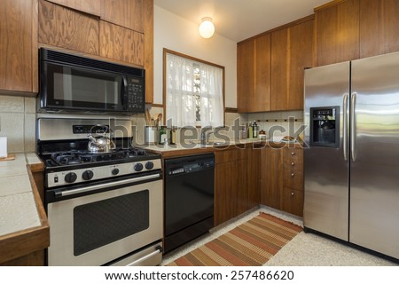 Traditional designed kitchen with wooden cabinets, stainless steel appliances and granite - stock photo