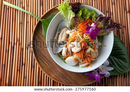 Traditional dish of freshly prepared Thai food.  Thai seafood and som tum green papaya salad. - stock photo