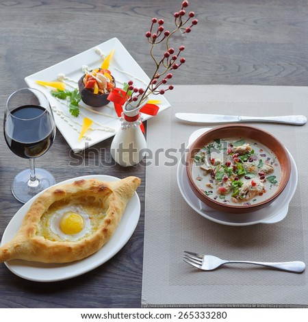 traditional dish of georgian cuisine, khachapuri, a soup, a glass of wine - stock photo