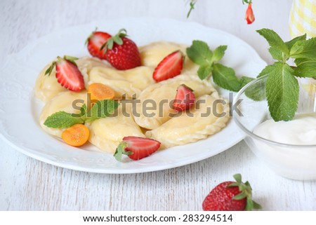 Traditional dish of Slavic cuisine. Curd -filled varenyky with mint and strawberries on a white plate.  Raw Russian traditional vareniki with cottage cheese.