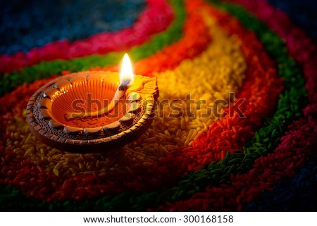 Traditional diya lamp lit on colorful rangoli - stock photo