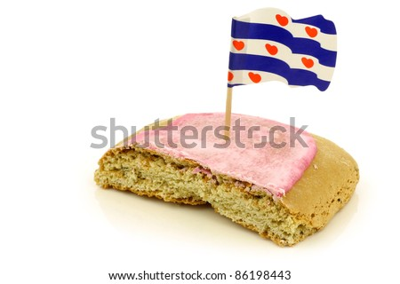 "traditional Dutch and Frisian pink glazed pastry called ""fondant koek"" with a frisian flag toothpick on a white background - stock photo"