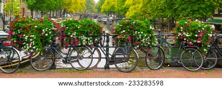 Traditional dutch bicycles parked on canal in Amsterdam - stock photo