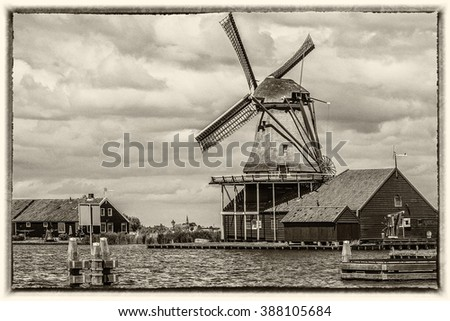 Traditional Dutch old wooden windmill in Zaanse Schans - museum village in Zaandam. The Netherlands. Style of an old photo. - stock photo