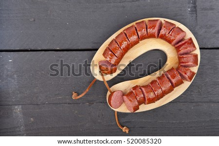 Traditional Dutch smoked sausage called Rookworst on wooden background